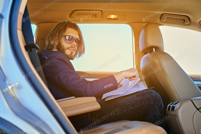A man sits in a car and working with paper documents.