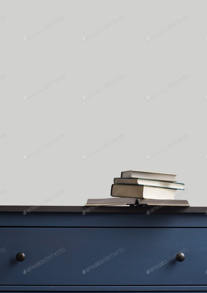 stack of books on blue chest of drawers