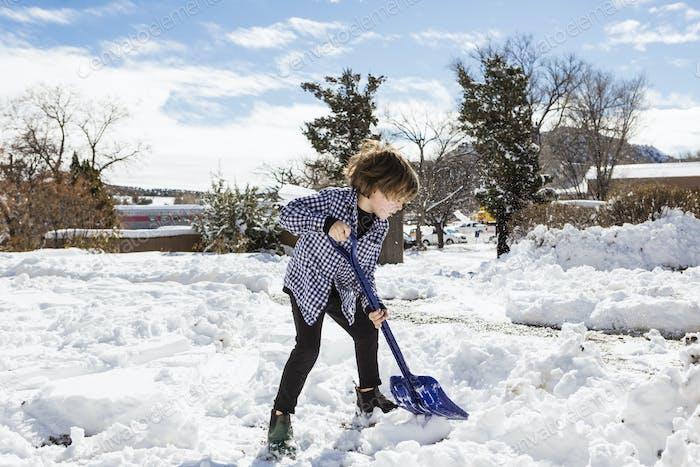 Ein sechsjähriger Junge schaufelt Schnee in der Einfahrt