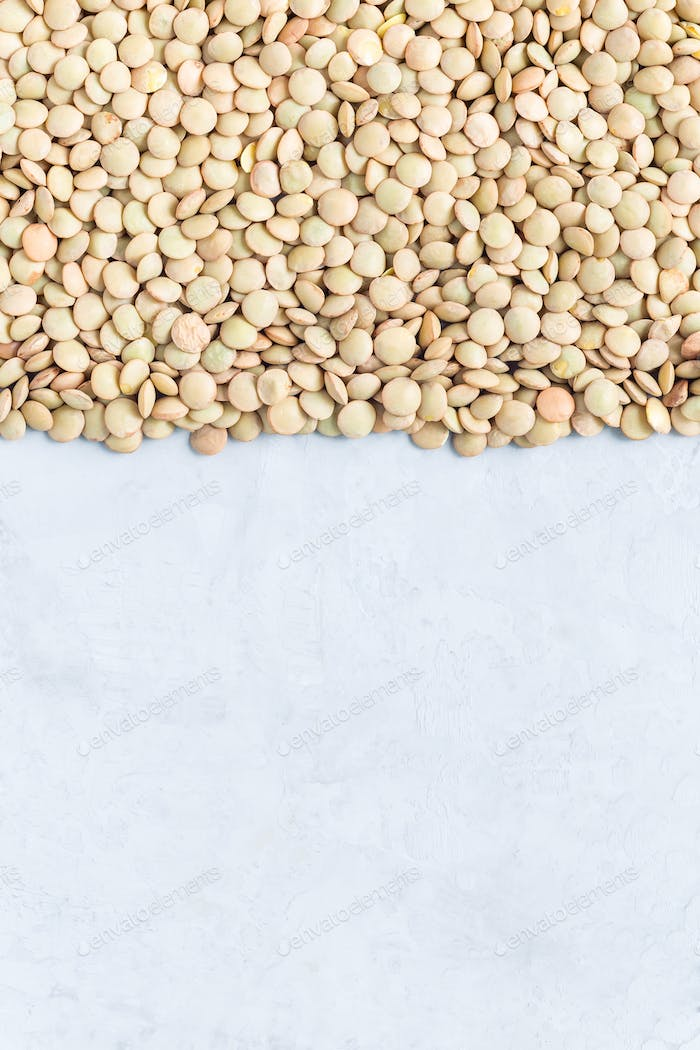 Uncooked dry green lentils, vertical, copy space, top view