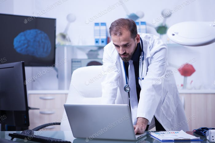 Doctor working on his laptop and checking the treatment of his patients