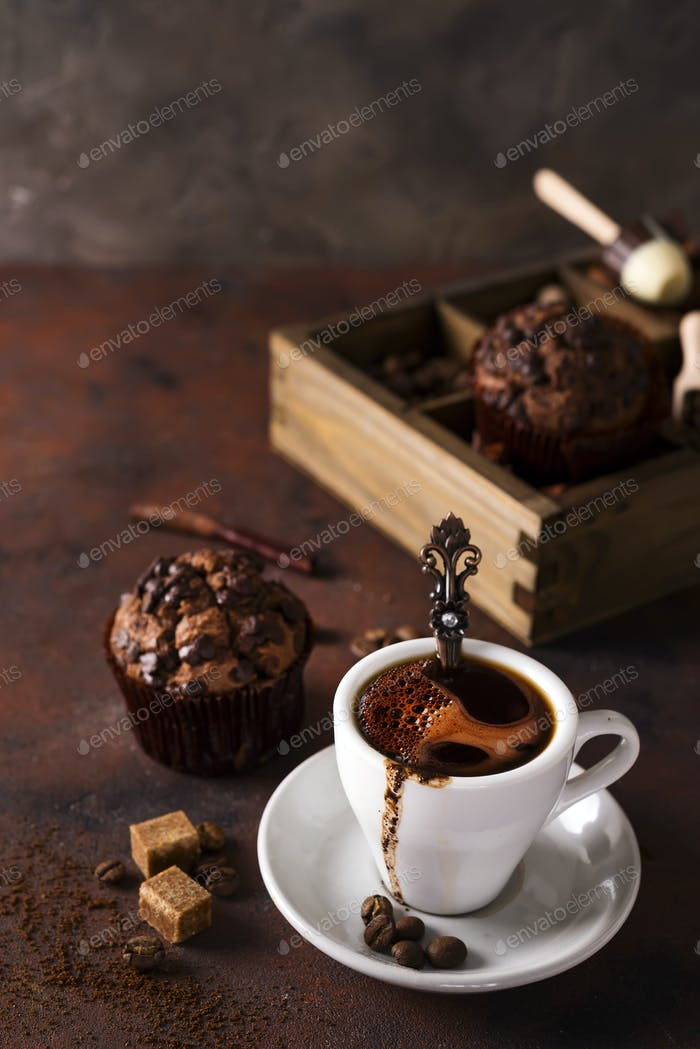Cup of coffee with cooffee beans, wooden box with grains of coffee and spices, cupcake