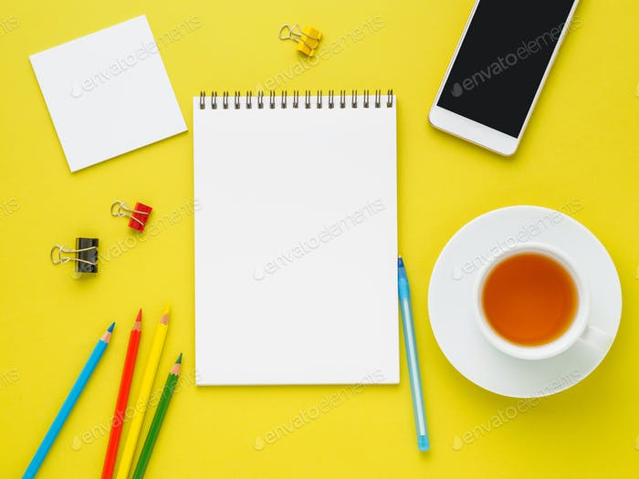Top view of modern bright yellow office desktop with blank notepad, cup of tea and supplies