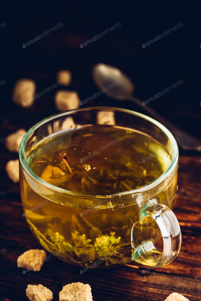 Cup of herbal tea with refined sugar