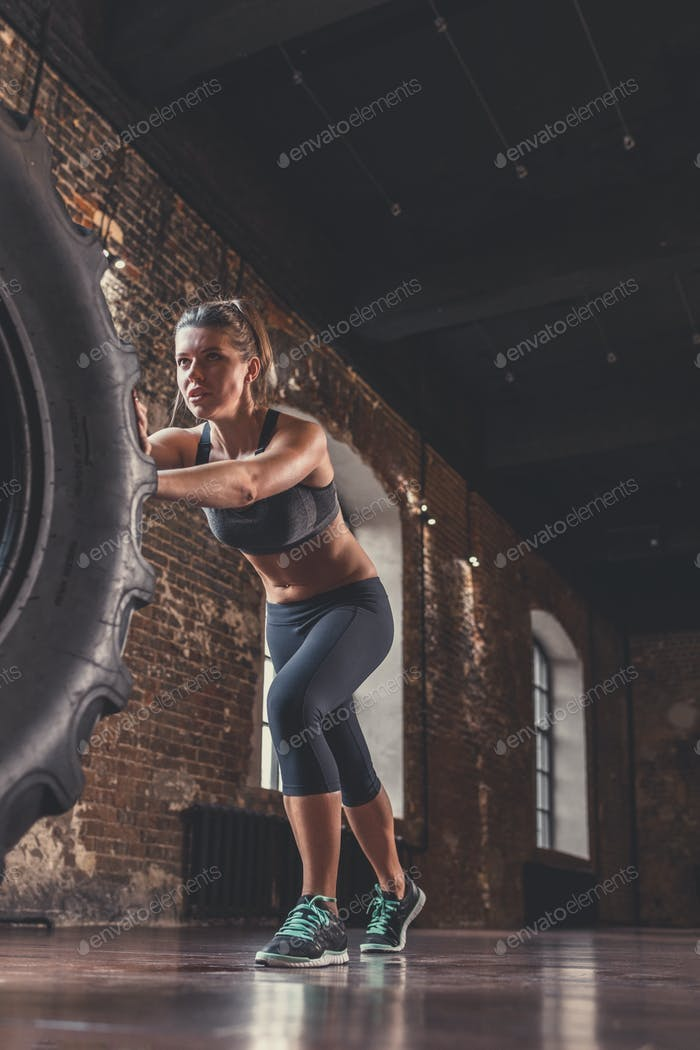 Athletic woman with a crossfit wheel