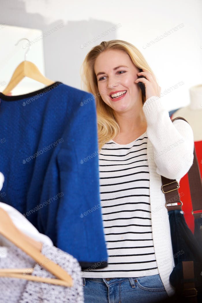 happy young blond woman shopping for clothes and talking on cellphone