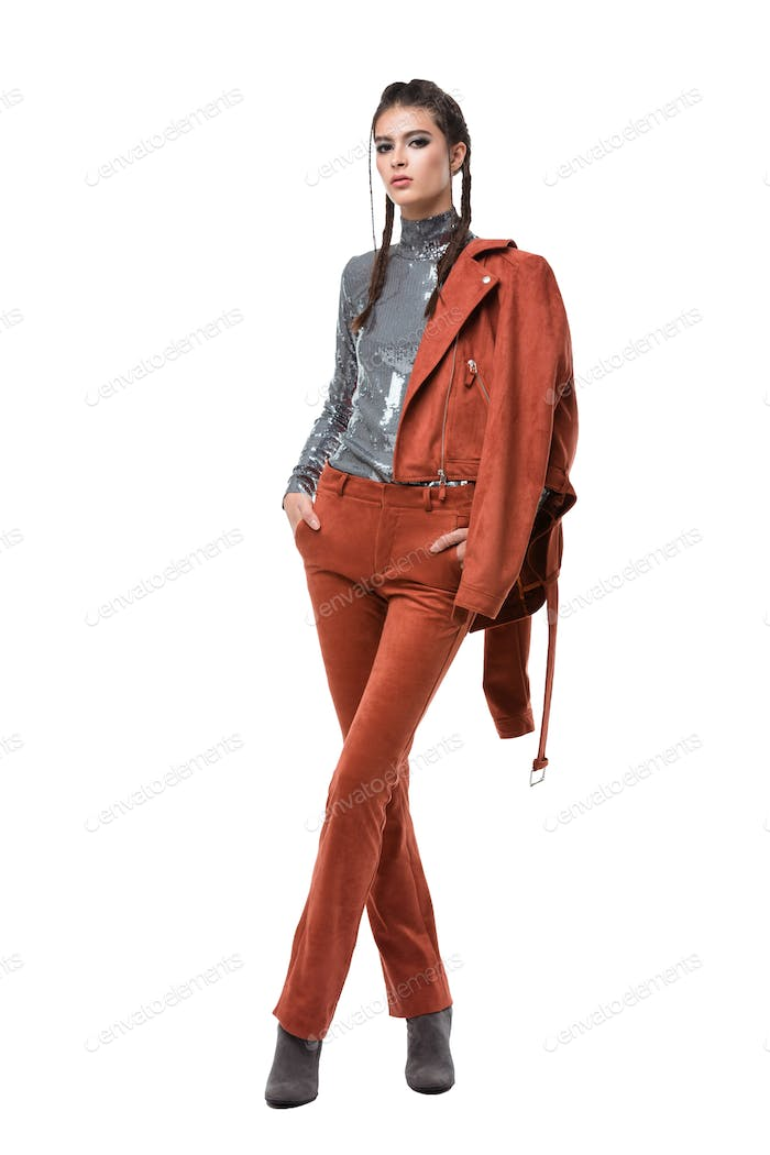 Beautiful girl standing in ginger suede jacket and trousers and silver top with sequins