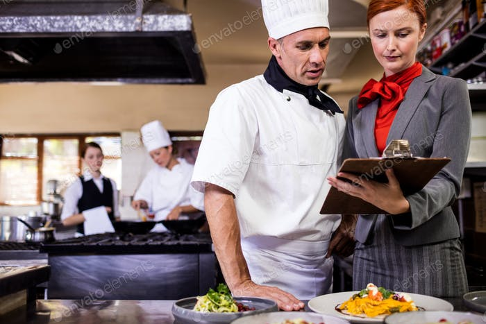 Female manager and male chef writing on clipboard in kitchen at hotel