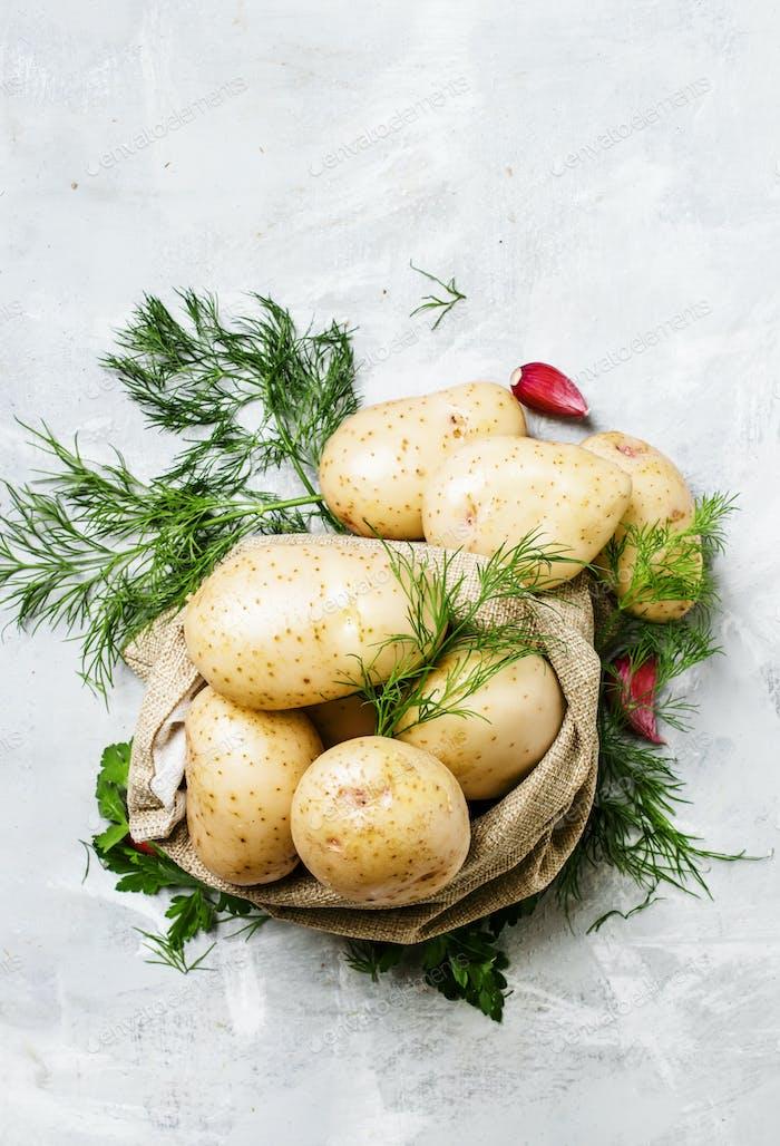 Frische junge Kartoffeln in einer Leinentasche, Dill, Petersilie und Knoblauch