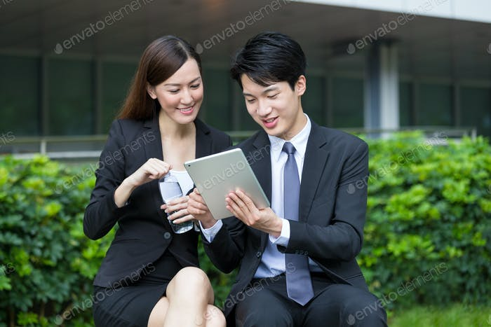 Businesswoman reading something on digital tablet with businessman