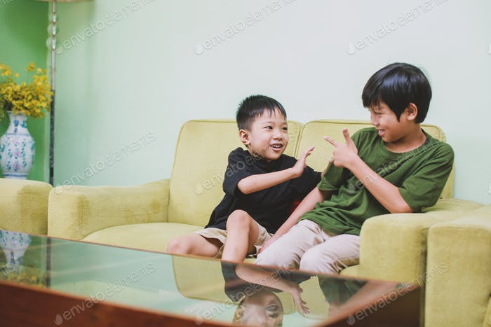 Asian brothers playing and joking on couch