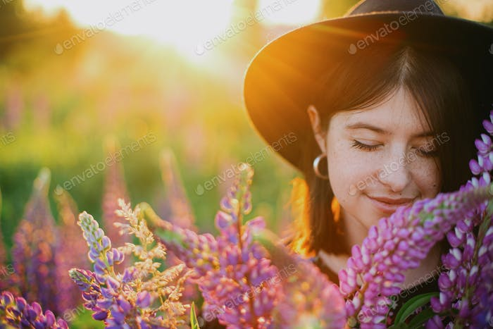 Portrait of woman with lupine bouquet in sunset light in countryside field. Atmospheric moment
