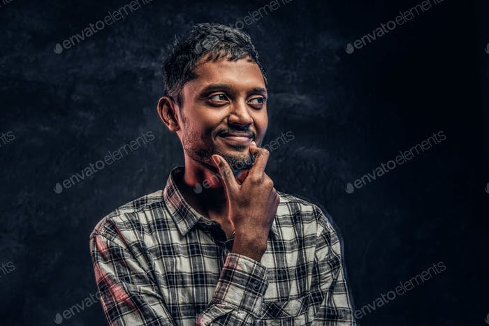 Portrait of a handsome young Indian guy wearing a checkered shirt holding hand on chin