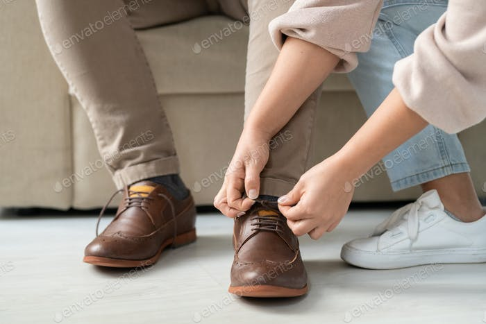Hands of careful woman helping her sick disable father to tie shoelaces on boots