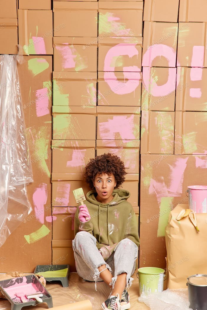 House renewal concept. Shocked dark skinned curly female painter sits on floor being tired after pai