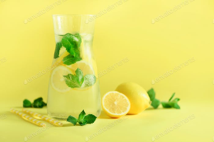 Fresh summer fruits water or lemonade with mint, ice, lemon on yellow background. Copy space. Summer