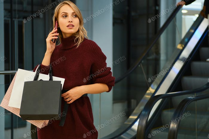 Beautiful blond girl in knitted sweater confidently talking on cellphone in shopping mall