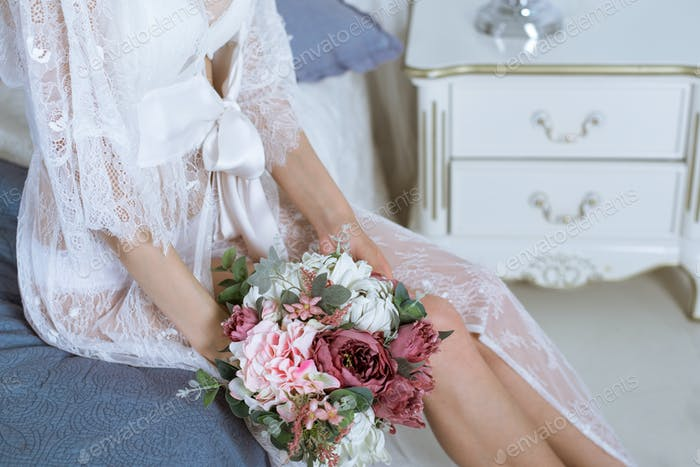 Beautiful sexy lady in elegant white robe and bouquet