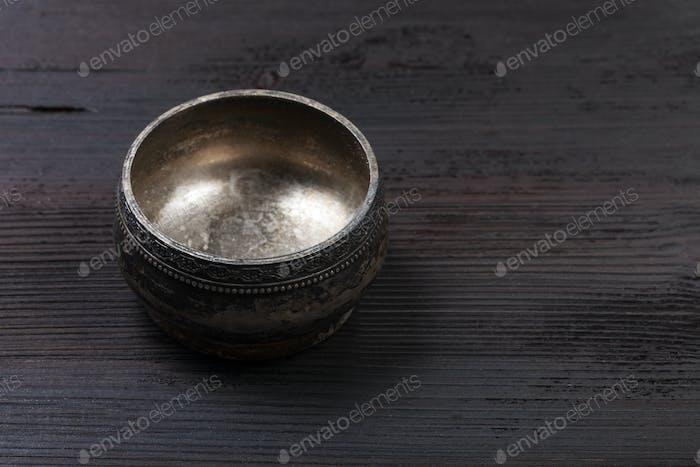 empty vintage silver salt cellar on wooden board