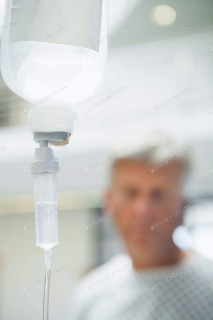 Intravenous drip with patient in background in hospital