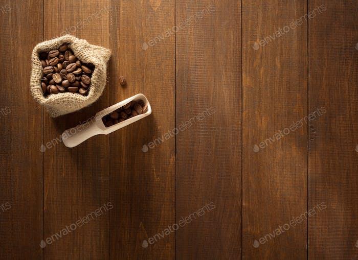 Kaffeebohnen im Beutel auf Holz