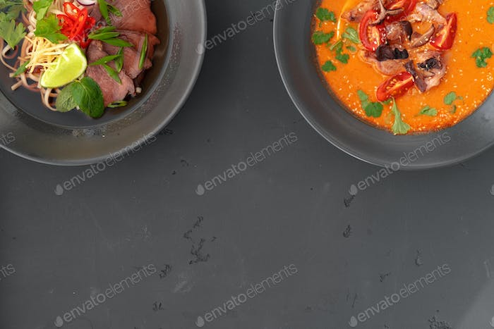 Tom Yam soup and Ramen soup in bowls on gray background