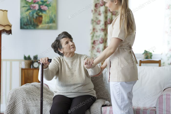 Nurse helping elderly woman to stand up