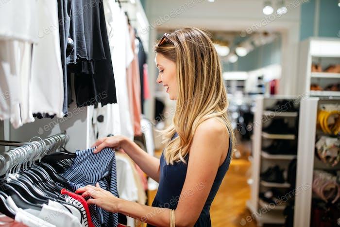 Verkauf, Mode, Konsum und Menschen Konzept. Glückliche junge Frau Wahl Kleidung in Mall