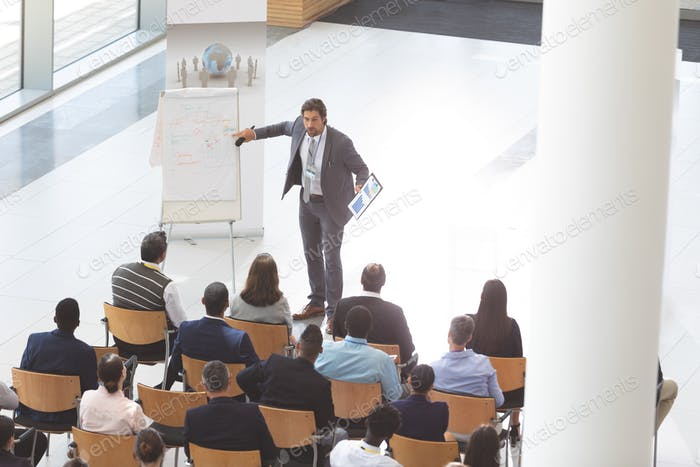 Businessman speaking and holding digital tablet and microphone at conference room.