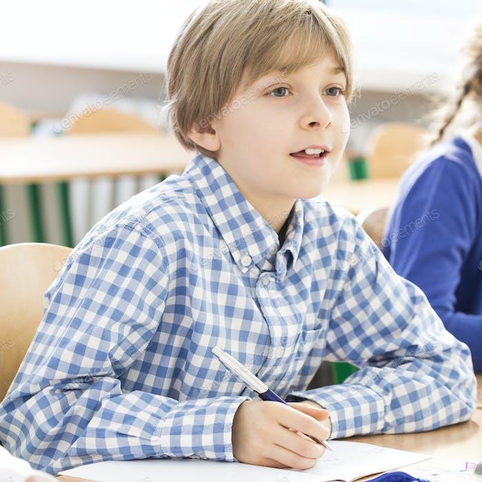 Kleiner Junge während des Unterrichts schreiben