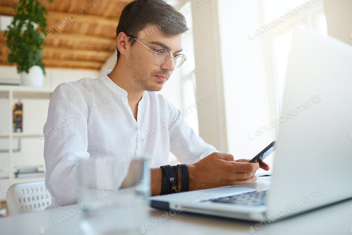 pensive handsome young businessman wears white shirt and glasses using laptop and mobile phone