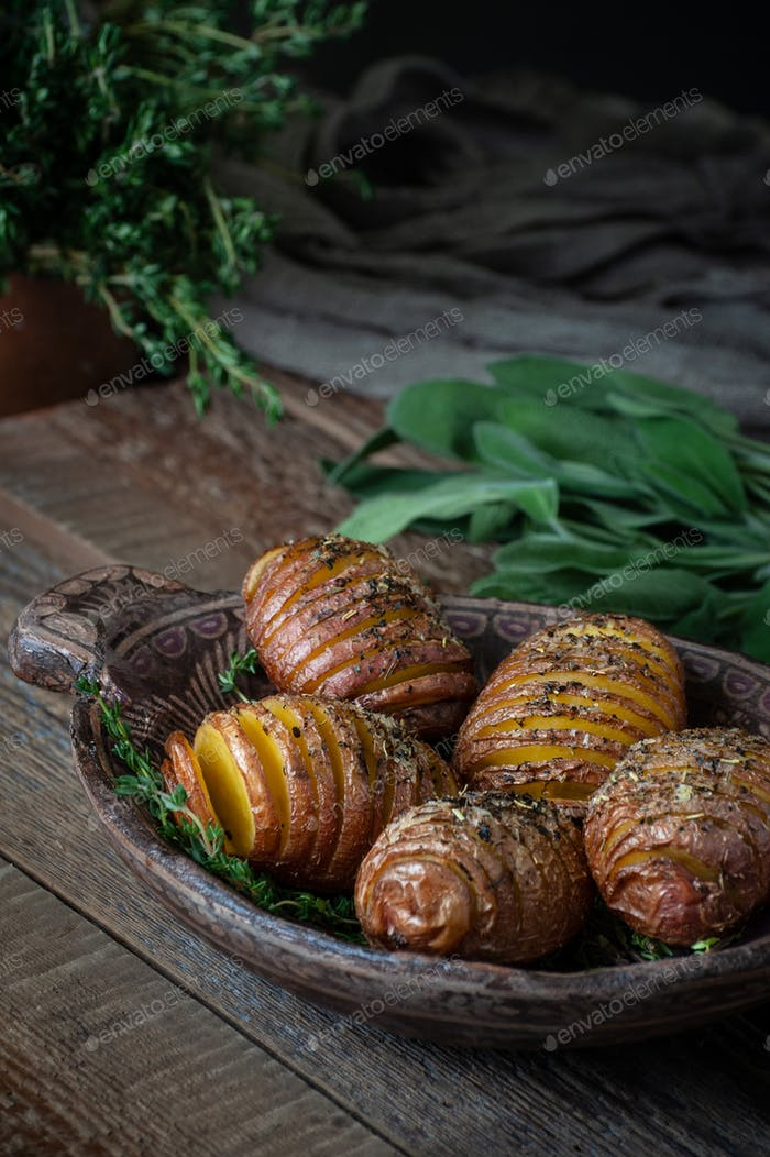 Whole baked potatoes with thyme in a wooden plate on an old rust