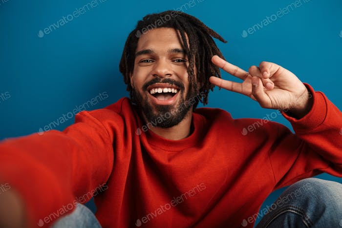 Portrait of african american man taking selfie and gesturing peace sign