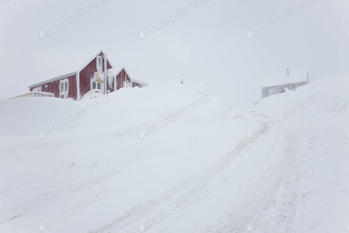 Winter landscape with snow-covered road leading to red wooden cottage on a hill.