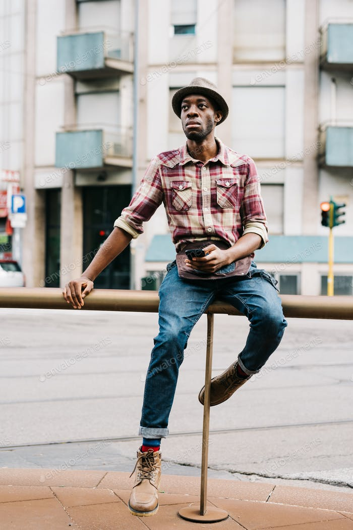 young handsome afro black man sitting on a handrail outside in t