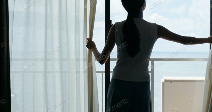 Frau öffnen Sie den Vorhang zu Hause