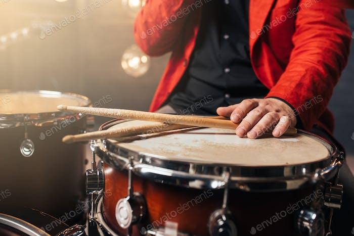 Männlicher Schlagzeuger im roten Anzug sitzt hinter Trommelset