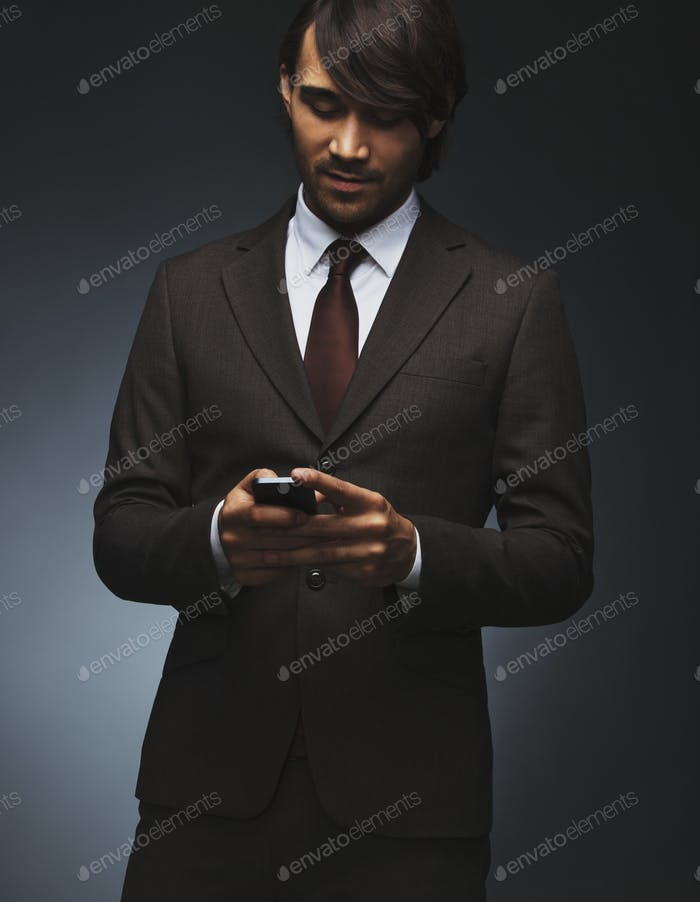Business man text messaging on his smartphone