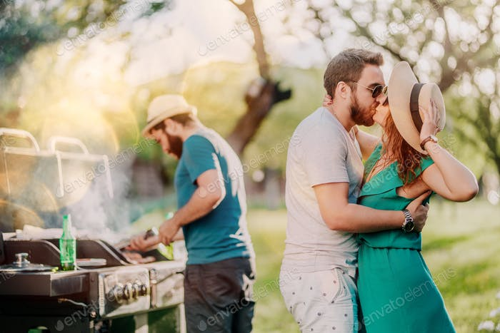 Portrait of perfect caucasian couple kissing at barbecue party