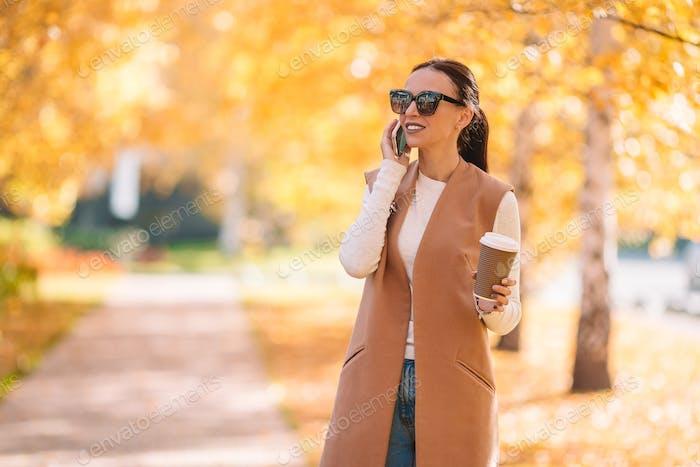 Herbst-Konzept - schöne Frau trinken Kaffee im Herbst Park unter Herbstlaub