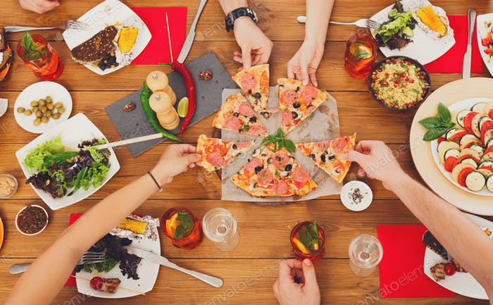 People eat pizza at festive table dinner party