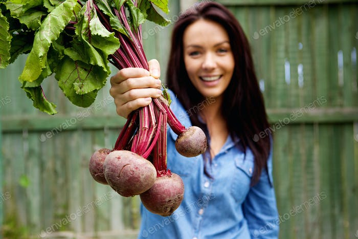 Smiling woman showing a bunch of beetroots