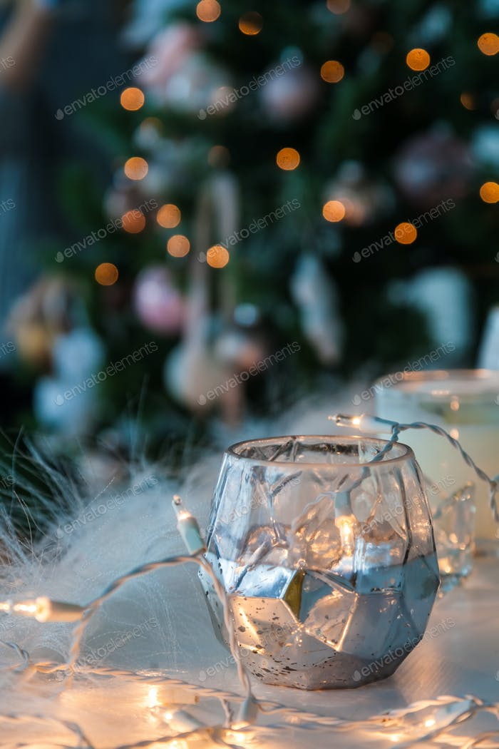 Candle holder with christmas lights and atmospheric light on background