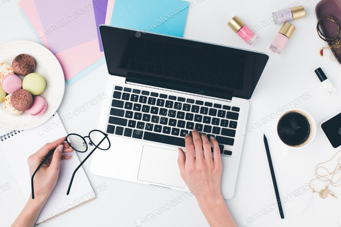 top view of woman using laptop at girly workplace