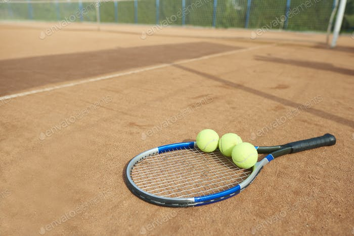 Tennis balls and tennis racket on the foreground
