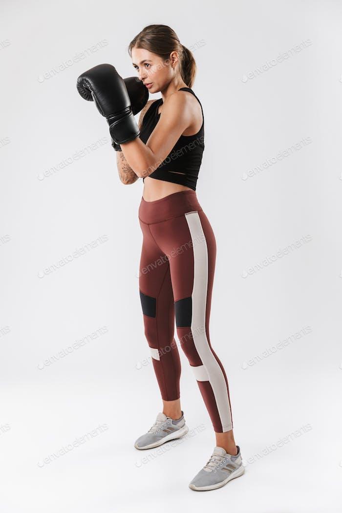 Bild einer starken Frau, die Sportbekleidung Training in Boxhandschuhen trägt