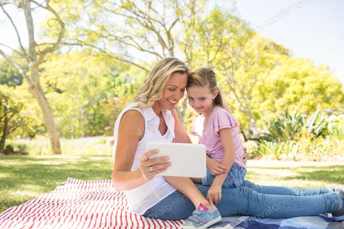 Happy mother and daughter using digital tablet in park