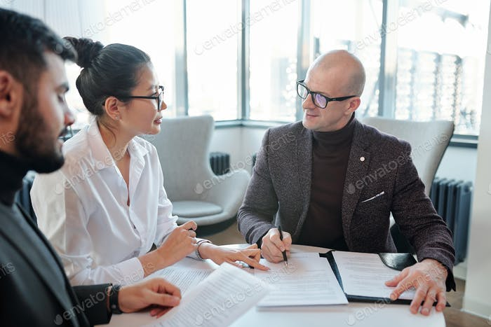 Young Asian female agent looking at business partner going to sign contract