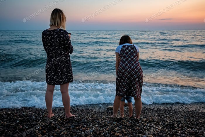 Back view family by the sea in evening