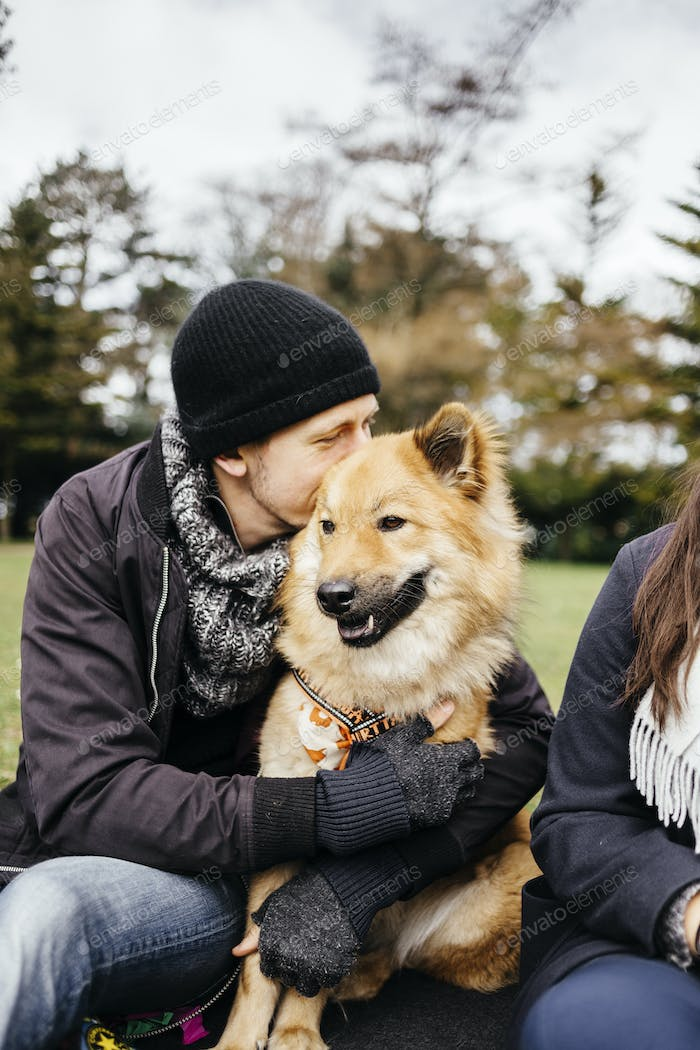 Man embracing Eurasier while sitting with woman at park